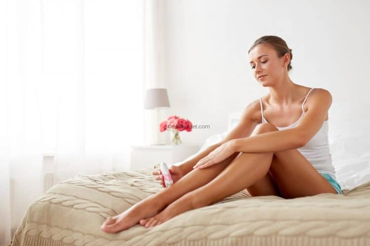 Woman epilating on the bed